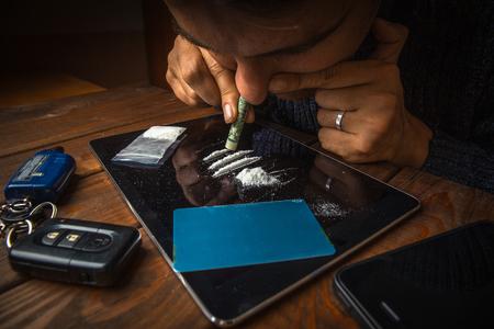 Hombre adicto a las drogas usando o inhalando cocaína por la nariz con un dólar enrollado de tableta, concepto de abuso de drogas
