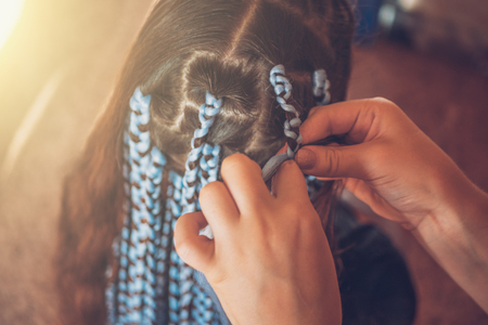 Hairdresser weaves braids with kanekalon material to young girl head, making creative hairstyle with thick plaits or pigtails also known as African or Afro braids, close up Reklamní fotografie