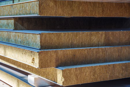 Stack of modern sandwich panel blocks from metal profile and wool foam for building warm and sound protected houses.