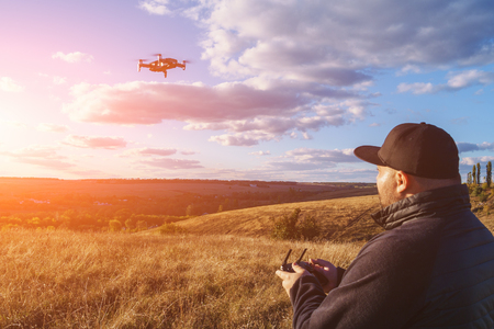 Man with remote controller operating flying drone or quad copter - modern small aircraft for aerial video making, toned Reklamní fotografie