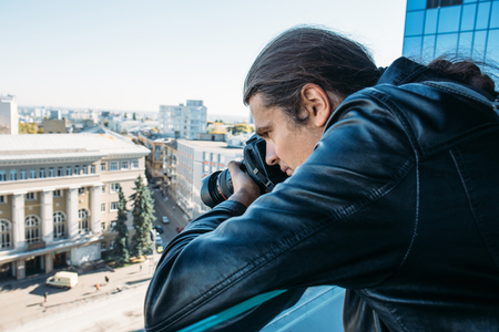 Investigator or private detective or reporter or paparazzi taking photo from balcony of a tall building with professional camera Reklamní fotografie