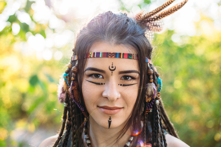 Happy young beautiful girl in image of native American smiles and looks at camera in sunny summer day