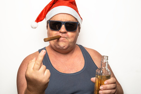 Funny mature man in character of Bad Santa Claus in sunglasses, cigar and bottle of alcohol shows middle finger sign in camera on white background