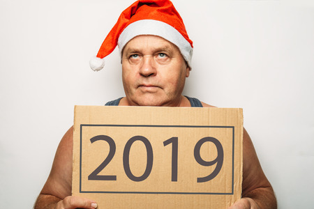 Funny senior serious man in red Santa hat holds cardboard with 2019 numbers in hands and looking up thoughtfully.