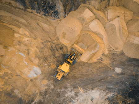 Yellow excavator or bulldozer works on construction site with sand, aerial or top view.