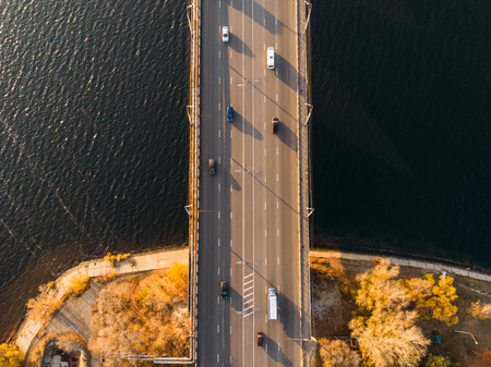 Aerial or top view from drone of concrete bridge with asphalt road or highway over big river with city car traffic, urban transportation, toned