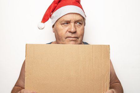 Funny serious mature man in red Christmas Santa hat holds empty cardboard as blank or mock up with copy space for text.
