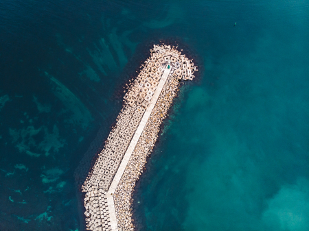 Stone breakwater with lighthouse in turquoise sea water, top view.