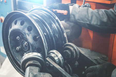 Repair and restoration of car wheel drive by mechanic master on professional machine equipment tool in car repair garage service, toned