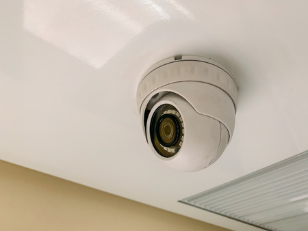 Security CCTV camera at ceiling in train corridor inside, close up