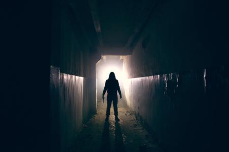 Silhouette de maniaque avec un couteau à la main dans un long couloir sombre et effrayant, un psychopathe d'horreur ou un concept de tueur en série, tonique