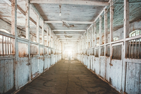 Inside old wooden stable or barn with horse boxes, tunnel or corridor view with light in the end, toned