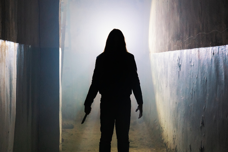 Silhouette of criminal or maniac with knife in hand in old scary building, serial killer with cold weapon, toned Zdjęcie Seryjne