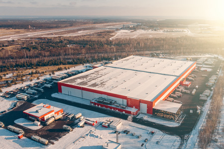 Aerial view of warehouse storages or industrial factory or logistics center from above. Top view of industrial buildings and trucks in winter landscape 스톡 콘텐츠
