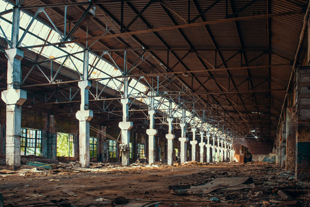 Ruins of abandoned factory or warehouse with columns, large creepy and empty industrial constriction, toned