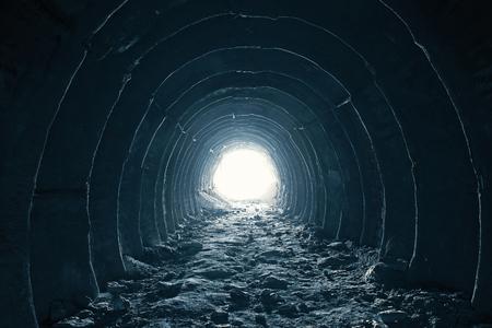 Dunkler runder Tunnel mit Licht am Ende, abstrakter Weg zur Freiheit und Hoffnung auf ein glückliches Lebenskonzept.