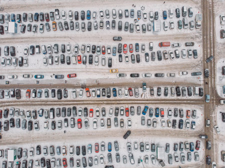 Parking lot with many cars near mall or shopping center in winter with snow, aerial view, drone photo from above Stock Photo