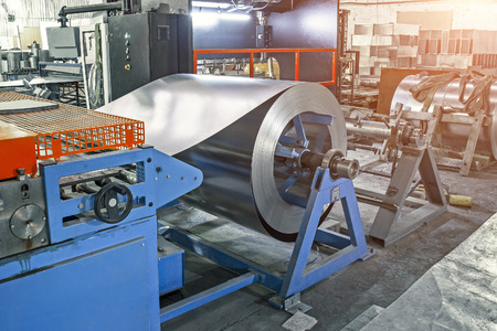 Worksop with machinery tools and equipment, rolls of galvanized steel for production metal pipes and tubes in factory, toned