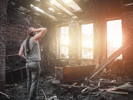 Man house owner stands inside his burnt house interior with burned furniture in arson and holding head by hand, fire aftermath and property insurance concept.