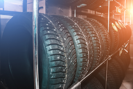 New winter studded tyre with metal spikes in store shelf, rubber auto car wheels with blue and red light effect