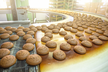 Bakery production line or with fresh sweet cookies on conveyor belt. Equipment machinery in confectionary factory workshop, industrial food production. Stock Photo