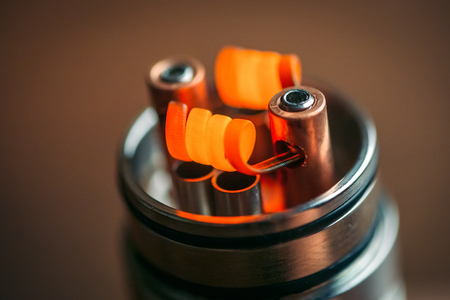Warming up to red new Alien Clapton Coils on vape device RDA, macro photo.