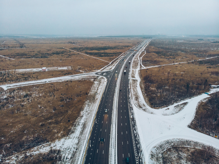 Aerial or top view from drone to winter asphalt highway or motorway road in countryside with cars and cargo logistic trucks traffic driving fast Фото со стока