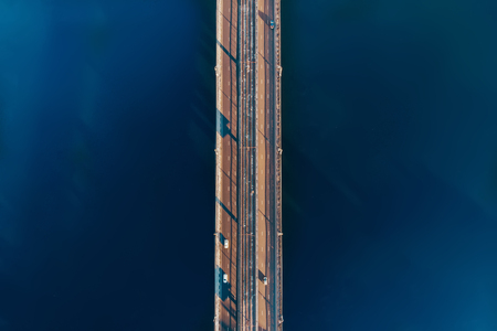 Aerial or top view from drone of concrete bridge with asphalt road or highway over big river with city car traffic, urban transportation concept Standard-Bild