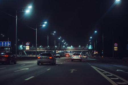 Urban city traffic cars in night illuminated asphalt city road, abstract cityscape transportation concept, toned