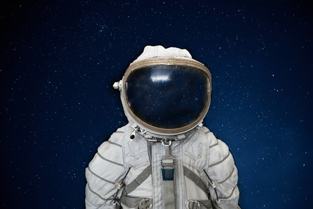 Soviet cosmonaut or astronaut or spaceman suit and helmet on black space with stars background, close up