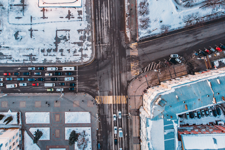 Aerial shot from drone of winter city with snow, roads, cars traffic and buildings top down view.