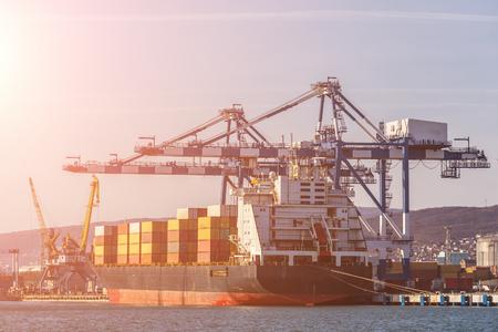 Contenedores en barco de carga en puerto marítimo industrial para envío y logística, grúas y otros equipos especiales, concepto de entrega de comercio internacional, tonificado Foto de archivo