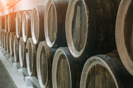 Wine cellar and rows of barrels with liquor or alcohol, closeup toned
