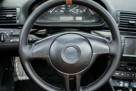 Luxury car interior with dashboard, steering wheel and leather seats, close up. Stockfoto
