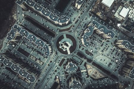 Top down aerial view of round road intersection with cars and new modern buildings, drone shot, toned