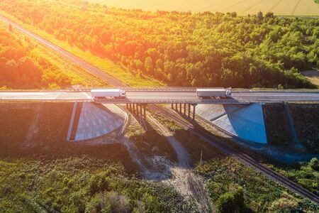Aerial view of truck with cargo driving on highway route bridge in sunset light, industrial transportation and logistics concept Reklamní fotografie