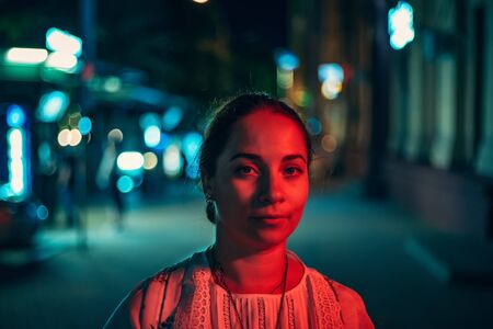 Portrait of young pretty girl looking at camera in red light on her face on night city street with blurred illuminated urban background, toned