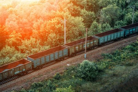 Freight train drive fast, railway wagons in sunlight. Transportation, railroad, toned Reklamní fotografie