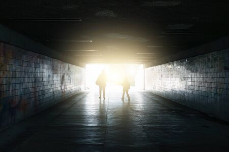 Silhouettes of woman and kid walk to light in end of underground tunnel, toned