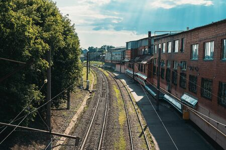 Railroad tracks in city landscape in sunny day, toned