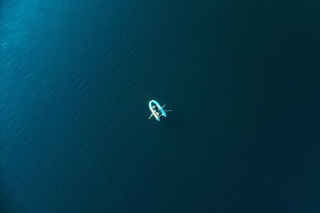 Boat with fisherman on blue sea water surface, aerial top view. Reklamní fotografie