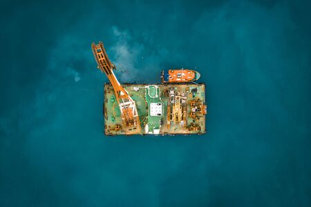 Industrial platform in ocean or tower with crane or science sea research center, aerial top view from drone, toned