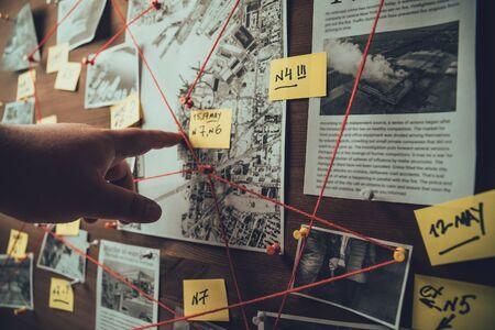 Tablero de detectives con fotos de presuntos delincuentes, escenas del crimen y evidencia con hilos rojos, enfoque selectivo, tonos retro