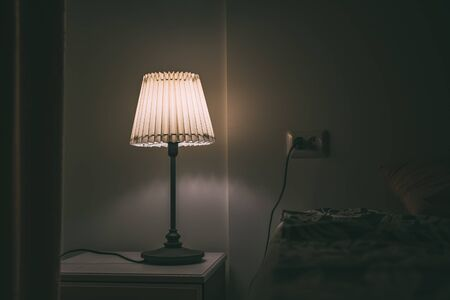 Bedroom lamp on night table in hotel room at night. Reklamní fotografie