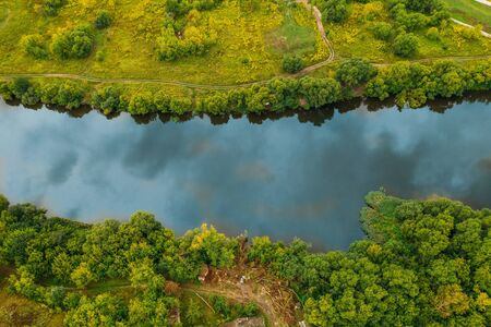 Aerial top down view of river among green summer landscape with reflection of blue sky with clouds.