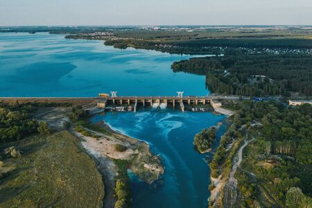 Aerial panoramic view of concrete Dam at reservoir with flowing water, hydroelectricity power station.