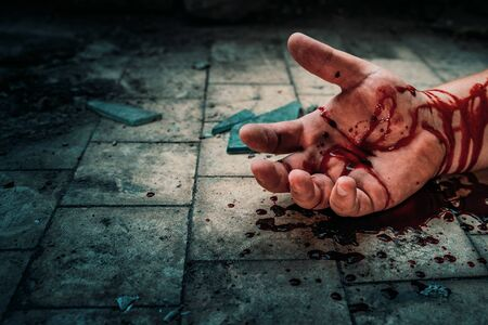 Crime scene with human hand in blood on floor of killed man by murder, dead body part close up.