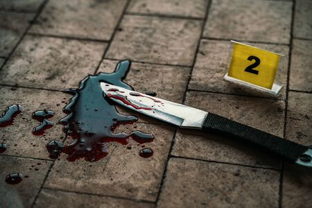 Crime scene with knife marked with number in blood of victim on floor. Investigation of cruel murder concept Stock Photo