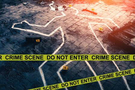 White chalk outline of killed body, blood an floor and yellow police caution tape with text - crime scene, do not enter. Murder investigation concept, toned Banco de Imagens