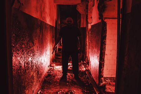 Serial killer silhouette with knife in hand in red corridor. Crime scene and trash horror maniac. Zdjęcie Seryjne